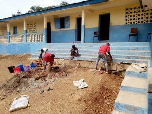 Mannen-repareren-de-afwatering-van-de-school-in-Heremakono